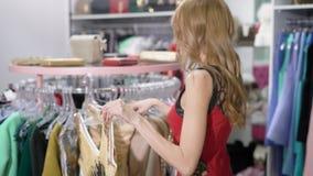 Съемка от заднего красивой женщины держа новое модное платье в торговом центре сток-видео