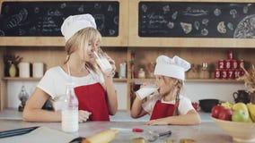Съемка портрета привлекательной матери и ее довольно маленькой дочери сидя в кухне и питьевом молоке крыто акции видеоматериалы