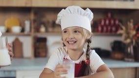 Съемка портрета привлекательной матери и ее довольно маленькой дочери сидя в кухне и питьевом молоке крыто видеоматериал