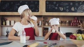 Съемка портрета привлекательной матери и ее довольно маленькой дочери сидя в кухне и питьевом молоке крыто сток-видео