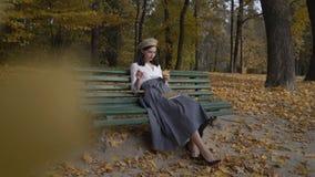 Съемка рискованного предприятия Stylization под женщиной тридцатых годов Черно-с волосами в берете и длинной юбке против фона  видеоматериал