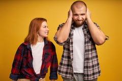 Съемка сердитой надоеданной красной женщины волос упрекает супруга, обвиняет во что-то кричит с досадливостью, разочарованным неб стоковое изображение rf