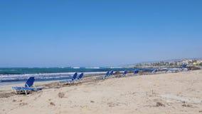 Съемка сиротливого песчаного пляжа с sunbed на бурный ветреный день Сильные волны ударяя и брызгая против seashore Slowm видеоматериал