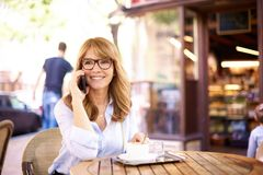 Съемка средней достигшей возраста женщины сидя в кофейне и звоня стоковые изображения