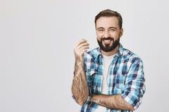 Съемка студии красивого бородатого человека в проверенной рубашке, пересекая одну руку пока поднимающ другие, смеющся над и жмуря стоковая фотография