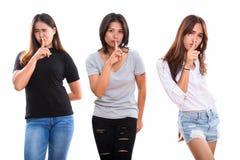 Съемка студии 3 молодых азиатских друзей женщины с пальцем на li стоковое изображение rf