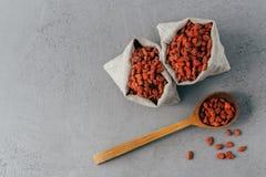 съемка сухих красных ягод goji в 2 небольших мешках и на деревянном tablespoon r Супер еда с противостарителями, стоковое фото rf