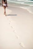 Съемка следов ноги с женщиной идет на тропический пляж стоковое фото