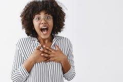 Съемка талии-вверх касанный удивленный и признательный привлекательный молодой женский сотрудник с темной кожей, афро стилем прич стоковое фото