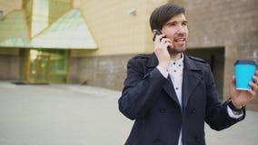 Съемка тележки молодого усмехаясь бизнесмена говоря на smartphone и чувствует счастливой о делать прогулки дела около офиса Стоковое фото RF