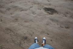 Съемка точки зрения взгляда человека вниз к его ногам стоя на проселочной дороге Стоковое Изображение RF