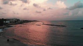 Съемка трутня людей идя вдоль пристани около океана на заходе солнца Вид с воздуха океана с туристской прогулкой на заходе солнца сток-видео