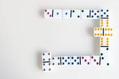 Съемка эффекта домино Посмотрите вниз для игры домино Домино понижаясь в ряд в фронт Части игры домино на белизне Стоковые Фото