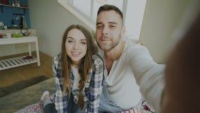 Съемка POV милых и любящих пар говоря онлайн видео- болтовню держа smartphone и беседуя к друзьям сидя в кровати видеоматериал