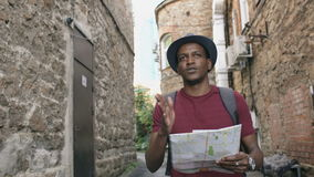 Съемка Steadicam Афро-американской туристской карты человека идя и наблюдая бумажной города для того чтобы найти направления к из акции видеоматериалы