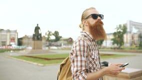 Съемка Steadicam бородатого туристского человека потеряла в городе и использовании карты онлайн smartphone для того чтобы найти п видеоматериал