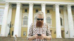 Съемка Steadicam бородатого туристского человека потеряла в городе и использовании карты онлайн smartphone для того чтобы найти п акции видеоматериалы