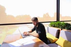 Съемщик количества работая на таблице кафа с бумагами и компьтер-книжкой Стоковые Изображения RF