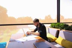 Съемщик количества работая на таблице кафа с бумагами и компьтер-книжкой Стоковое Фото