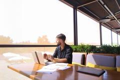 Съемщик количества работая на таблице кафа с бумагами и компьтер-книжкой Стоковая Фотография RF
