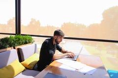 Съемщик количества работая на таблице кафа с бумагами и компьтер-книжкой Стоковая Фотография