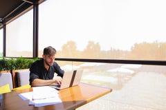 Съемщик количества работая на таблице кафа с бумагами и компьтер-книжкой Стоковые Фотографии RF