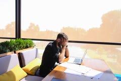 Съемщик количества работая на таблице кафа с бумагами и компьтер-книжкой Стоковые Фото