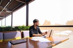 Съемщик количества работая на таблице кафа с бумагами и компьтер-книжкой Стоковые Изображения