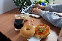 Съешьте закуски с питьем хлеба донута, воды пиццы и колы во время работы с компьтер-книжкой стоковое фото