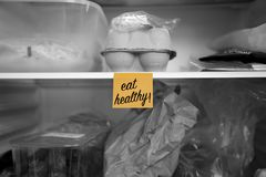 Съешьте здоровую написанную на столбе его примечание вставленное на полке холодильника с едой стоковая фотография rf