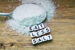 Съешьте меньше рекомендации соли с пластиковыми письмами и раздробленным солью на деревянной прерывая доске стоковое фото