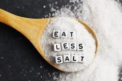 Съешьте меньше совета написанного с пластиковыми шариками письма на раздробленном соли – здоровый образ жизни соли еды стоковое изображение rf
