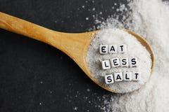 Съешьте меньше соли для уменьшения кровяного давления или риска гипертензии с взбрызнутым солью на темной предпосылке стоковое фото