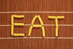 СЪЕШЬТЕ слово сделанное с сырцовыми элементами макаронных изделий на комплекте бамбука Стоковые Фотографии RF