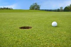 Сыграйте в гольф, шарик лежа на зеленом цвете рядом с отверстием Стоковое Фото