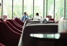 Сыгранность Бизнесмен и коммерсантка сидя на таблице в кофейне и обсуждают бизнес-план На таблице компьтер-книжка Стоковые Изображения RF