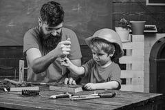 Сыгранность в концепции мастерской Будьте отцом, родитель с бородой уча, что маленький сын использовал отвертку инструмента Мальч стоковые фото