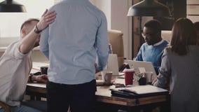 Сыгранность в современном здоровом рабочем месте Многонациональные бизнесмены сотрудничают, обсуждают проекты в дружественной обс видеоматериал