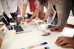 Сыгранность, коллективно обсуждать концепцию Молодые творческие менеджеры объединяются в команду работа с новым startup проектом  Стоковая Фотография