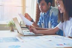 Сыгранность, молодая коммерсантка в офисе в вскользь рубашке Выбирать информацию с коллегами с компьютером Стоковое Фото