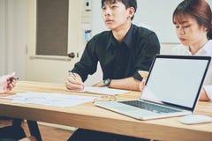 Сыгранность, молодая коммерсантка в офисе в вскользь рубашке Выбирать информацию с коллегами с компьютером Стоковая Фотография