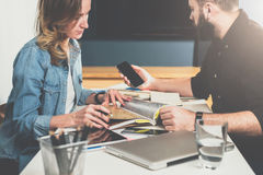Сыгранность, молодые дизайнеры сидит на таблице в офисе и выбирает вверх заканчивая материалы в каталоге Стоковые Фото