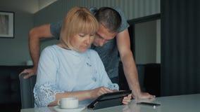 Сыгранность семьи Человек и женщина сидя на таблице с планшетом для того чтобы разрешить коммерческие задачи Обсуждение онлайн акции видеоматериалы