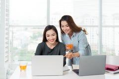 Сыгранность 2 усмехаясь молодых бизнес-леди сидя в офисе на Стоковое фото RF