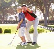 сынок игры гольфа отца учя к Стоковое Фото