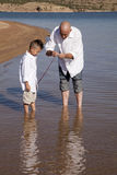 сынок рыб отца учит к Стоковые Фото