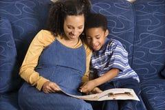 сынок чтения книги к женщине Стоковые Изображения