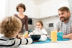 сынок чтения мамы кухни удерживания семьи папаа младенца к детенышам Стоковые Фото