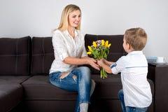 Сын дает его любимой матери красивый букет тюльпанов Концепция торжества, дня ` s женщин стоковое фото rf