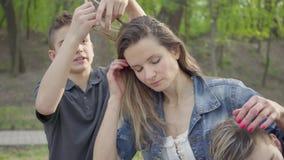 Сын делающ hairdress к его маме или няня пока они в парке на солнечном весеннем дне и говорить r акции видеоматериалы